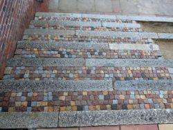 alte gebrauchte Granitkanten mit bunten Masaikpflaster als Auftritt