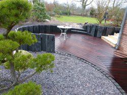 Holzterrasse mit Basaltstelen als Einfassung