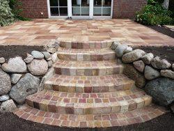 Stufen aus Sandsteinpalisaden und mit Sandsteinkleinpflaster ausgepflastert