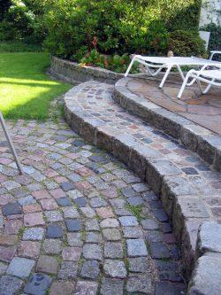 Buntes gebrauchtes Granitreihenpflaster als Stufe gemauert und den Auftritt mit Kleinpflaster ausgelegt und verfugt