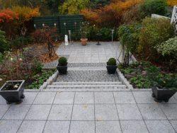 Granitplatten 40x40 cm in hellgrau und Stufen mit Granitstelen ausgepflastert mit Granitkleinpflaster 9x11cm.